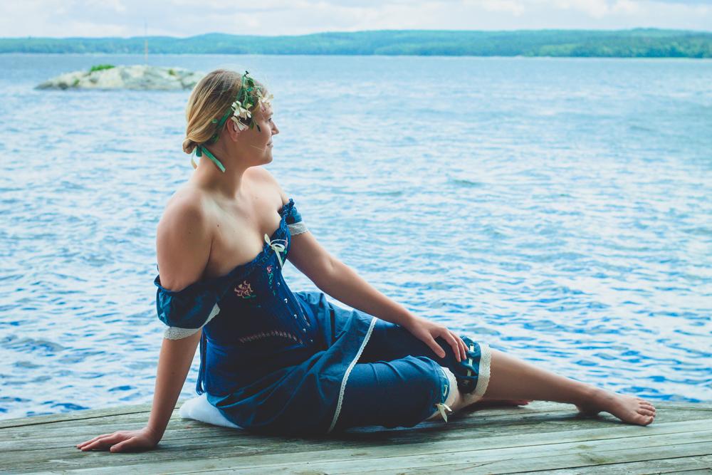 Kvinna i blå korsett på brygga vid vatten.