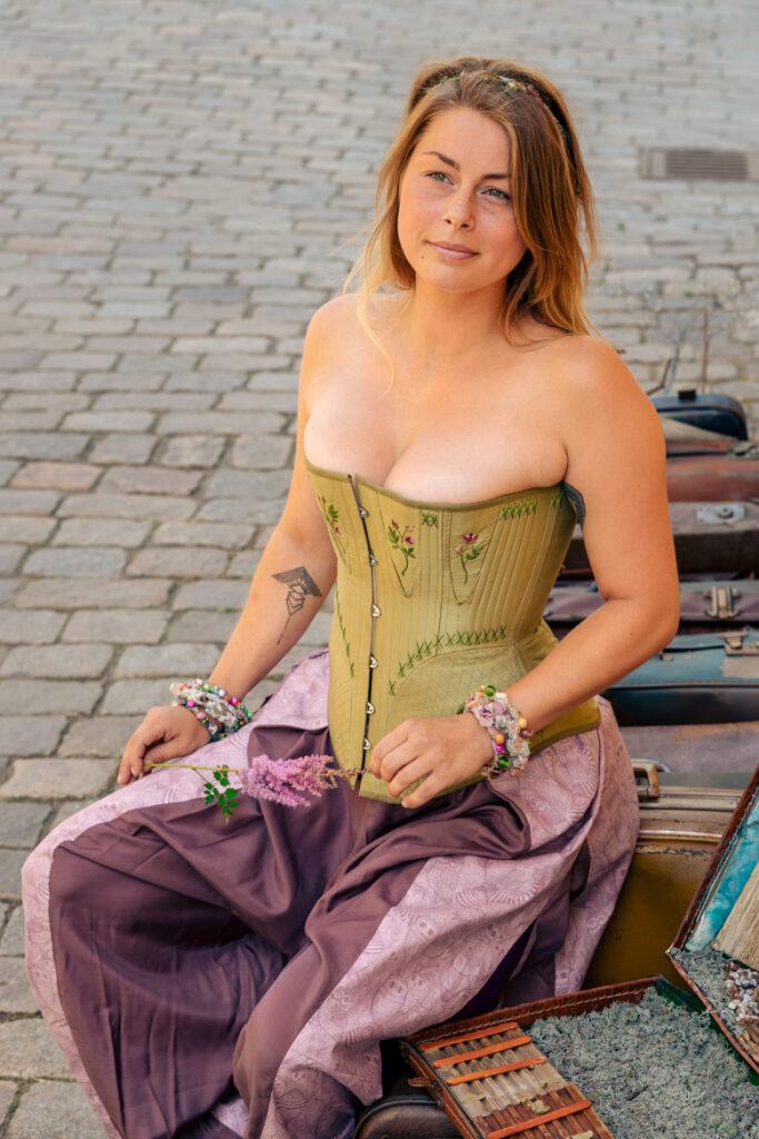 Kvinna med grön historisk korsett och lila haremsbyxor. Modell: Josefin Björnarås. Fotograf: Johanna Ene för Mytomsydd 2021.